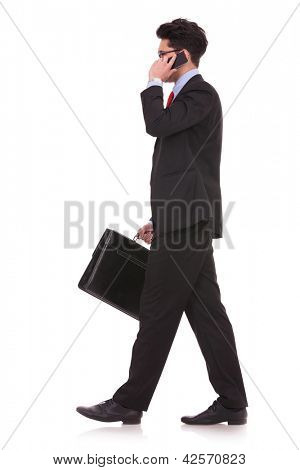 side view full length picture of a young business man  walking forward with a briefcase in one of his hands and talking at the phone while looking away from the cameraon white background