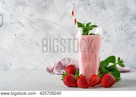 Strawberry Smoothie Or Milkshake With Berries And Mint In Tall Glass On Light Grey Background. Summe