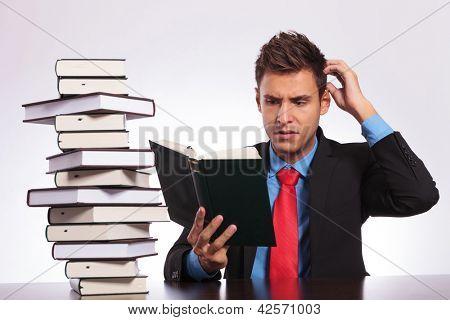 empresario joven confundido de lo que está leyendo en su escritorio