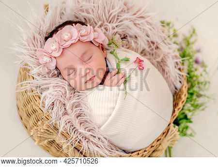 Portrait of beautiful newborn baby girl swaadled in fabric and wearing wreath with flowers sleeping in basket with fur during studio photoshoot. Cute infant child napping