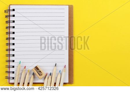 Back To School.on A Yellow Background - A Notebook, Pencils With A Colored Pencil Lead And A Sharpen