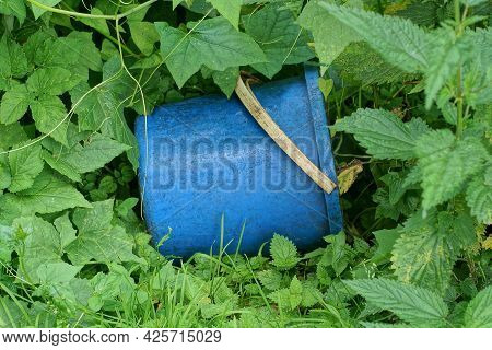 One Blue Dirty Plastic Bucket Lies In Green Grass And Vegetation Outside
