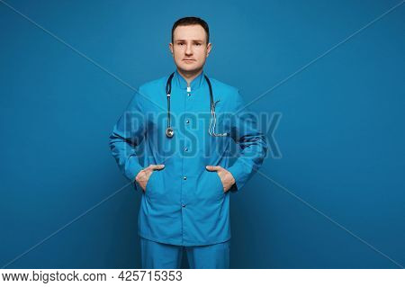 A Male Doctor In Medical Uniform Looking At The Camera And Posing In The Blue Background. Young Doct