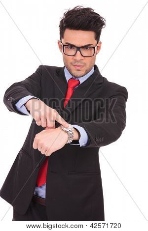 young business man pointing angrily to his watch and looking at the camera, on a white background