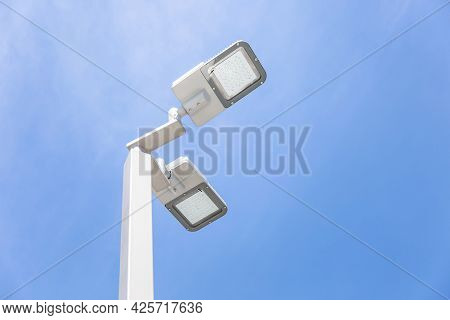 Led Street Lamp Post Glowing Blue Sky With White Cloud Background. Modern Led Lights In City