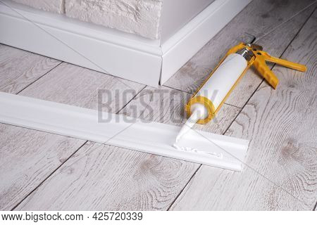 Applying Glue To The Skirting Board With A Glue Gun, Close-up