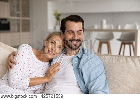 Close Up Dreamy Happy Couple Hugging, Relaxing On Couch Together