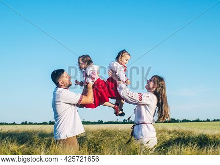 A Family In A Poppy Field Dressed In A National Slavic Costume. Mom, Dad And Twin Girls In Embroider