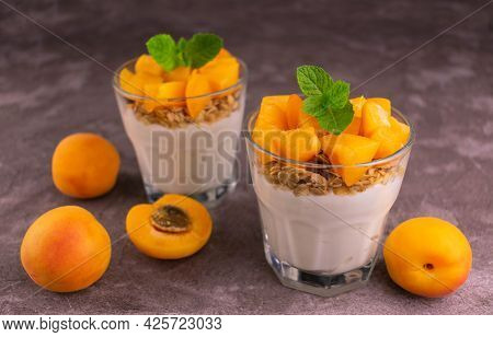 Two Bricot Yoghurt With Granola In Glasses On A Gray Background.
