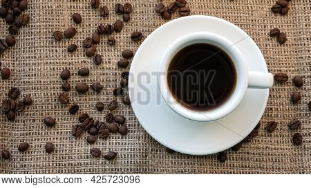 Coffee In A Cup Top View, Black Coffee Beans On A Fabric Bag, Aromatic Coffee Drink.