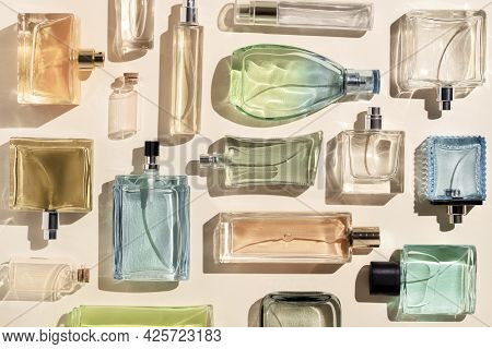 Perfume Bottles. A Lot Of Transparent Multicolored Glass Bottles Of Cosmetics, On A Beige Background