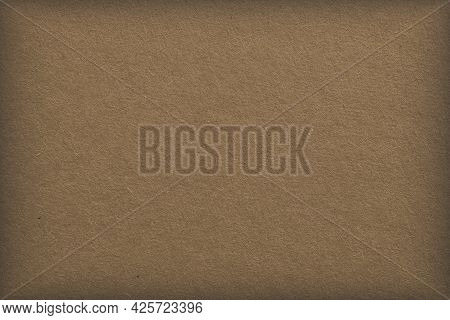 The Surface Of Brown Cardboard. Paper Texture With Cellulose Fibers. Background With A Pastel Tint A