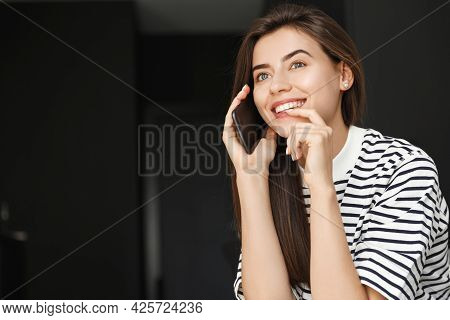 Portrait Of Happy Woman Having Phone Call. Girl Smiling, Sitting At Home With Smartphone, Talking On