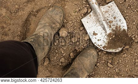 Farmer's Feet On The Ground, Shovel At Human Feet, Top View Of The Shovel. Agricultural Business. An