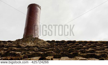 Heating Pipe On The Roof Of The House. Chimney On The Roof Of An Old House. Slate Roof.