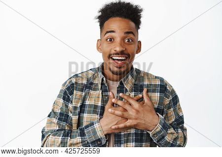 Moved And Touched African American Guy Being Grateful, Smiling Amazed And Happy, Holding Hands On He