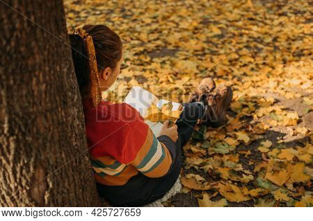 Young Plus Size Woman Reading Book In Fall Autumn Park In Sun Lights. Body Positive, Diversity, Body