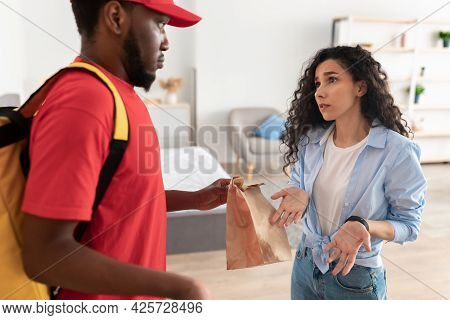 Portrait Of Confused Woman Unhappy About Food Delivery Mistake