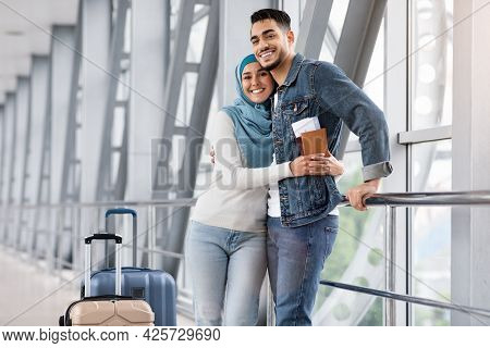 Happy Loving Muslim Spouses Embracing In Airport Terminal While Waiting Flight