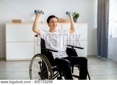 Physical Rehabilitation For Impaired People. Cheerful Disabled Teenager In Wheelchair Exerising With