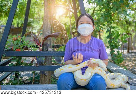 Young Girl Wear Mask And Hold An Albino Python, Pet Concept