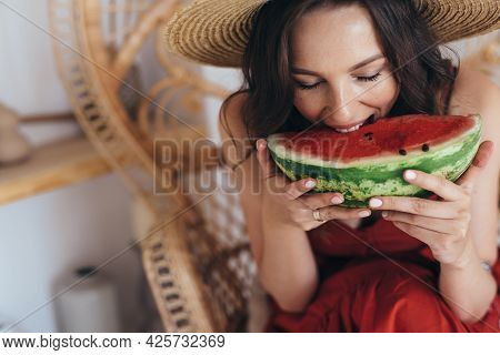 Young Woman Eats A Large Piece Of Watermelon