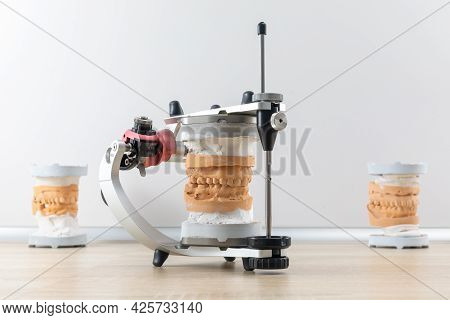 Dental Articulator With Dental Jaw Prosthesis Model On The Table In Dental Laboratory