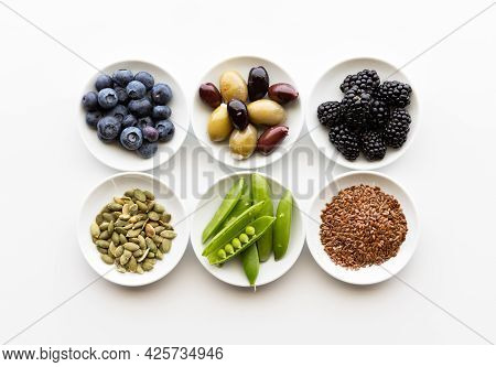 Top Down View Of A Small Dishes Of Various Healthy Ingredients Including Seeds, Vegetables, Olives A