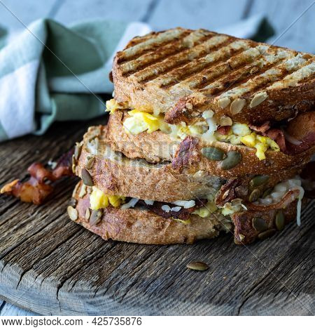 Two Grilled Breakfast Paninis With Egg And Bacon On A Rustic Wooden Board.