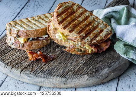 Grilled Breakfast Paninis On A Rustic Wooden Board, Ready For Eating.