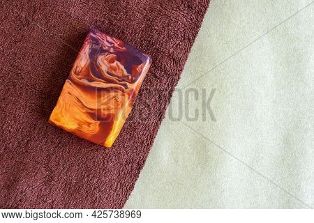 Piece Of Orange-brown Natural Handmade Soap On Braun Fluffy Terry Towel. Hygiene, Body Care And Heal