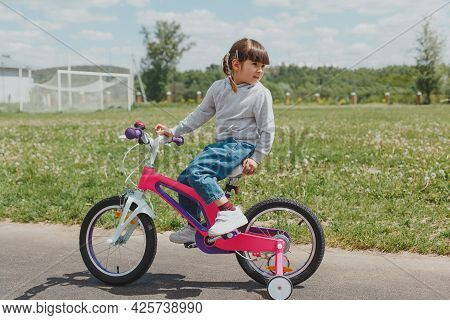 Little Cute Todler Girl In Jeans And A Sweatshirt With Pigtails Sits On A Pink Bike At The Stadium I