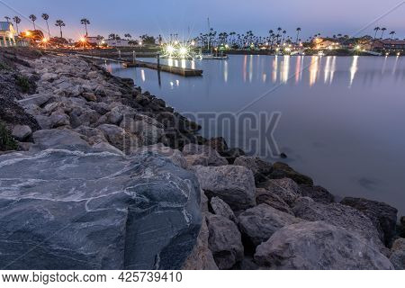 Textured Rocks Line The Harbor Cove Shoreline Leading Up To The Floating Docks Of The Marina.