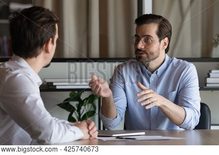 Confident Manager In Glasses Consulting Client At Meeting In Office