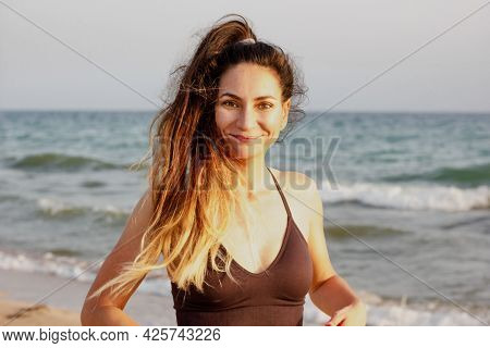Portrait Of A Sporty Fit Caucasian Woman Doing Fitness On A Beach, Wearing Sports Bra, Ponytail, Smi