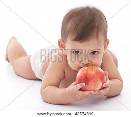 Baby girl attacking an apple. Isolated on a white background.