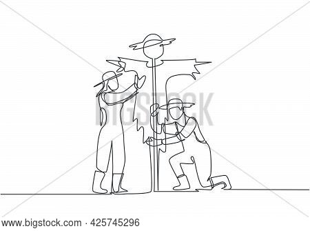 Single One Line Drawing Of Young Couple Farmer Is Installing A Scarecrow To Ward Off Pest Birds. Far