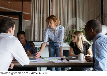 Confident Businesswoman Mentor Explaining Strategy, Leading Briefing With Diverse Employees