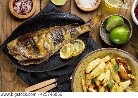 Baked Sea Bass Or Lingcod Fish With Potatoes On The Wooden Table