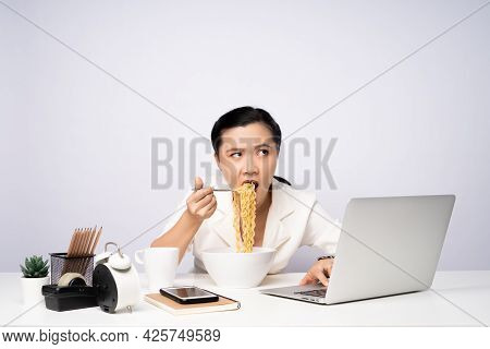 Asian Woman Working Hard Overtime Eating Instant Noodles At Office.