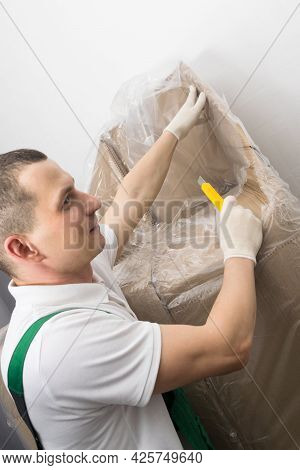 The Courier With A Smile Unpacks The Delivered Cargo With A Knife