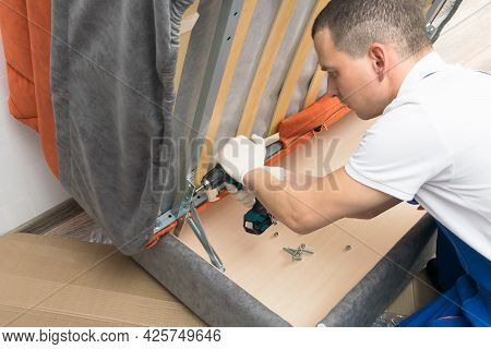 A Furniture Repair Worker Replacing The Creaking Mechanism Of An Upholstered Sofa
