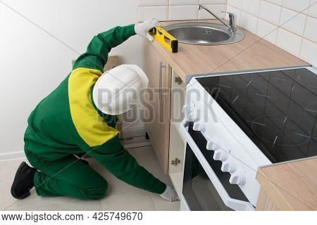 A Specialist Checks The Evenness Of The Installation Of Kitchen Furniture With A Tool, Turns The Cab