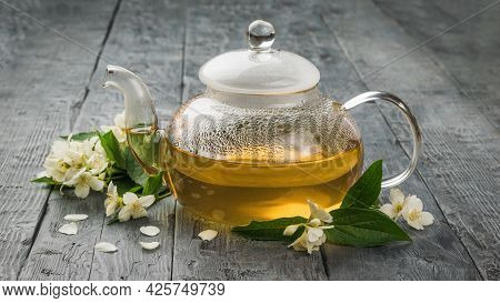 A Glass Teapot Filled With Medicinal Tea With Jasmine Flowers. An Invigorating Drink That Is Good Fo