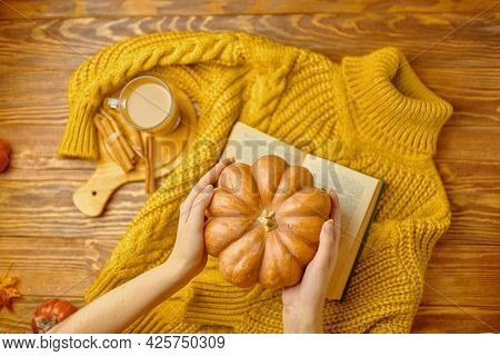 Round Pumpkin In Hands Over Warm Knitted Sweater. Aromatic Coffee With Cinnamon Sticks On Wooden Tra