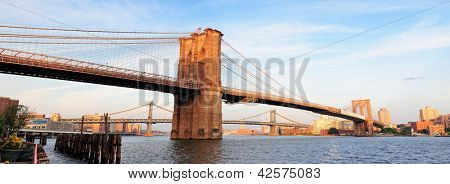 Brooklyn Bridge panorama view over East River viewed from New York City Lower Manhattan waterfront at sunset.