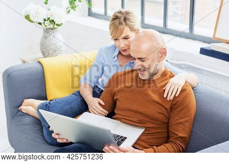 Smiling Middle Aged Couple Relaxing On The Sofa At Home Together While Browsing On The Web.