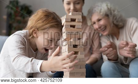 Young Mom And Retired Granny Playing Together With Preteen Girl
