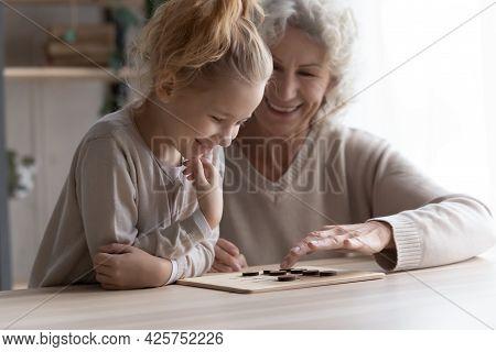 Elderly Female Babysitter Engaged In Logic Game With Preteen Girl