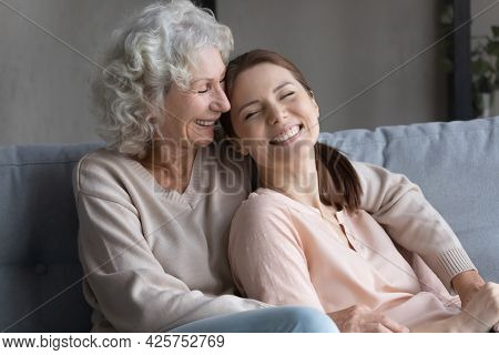 Smiling Woman Grown Up Child Lean Back To Senior Mom